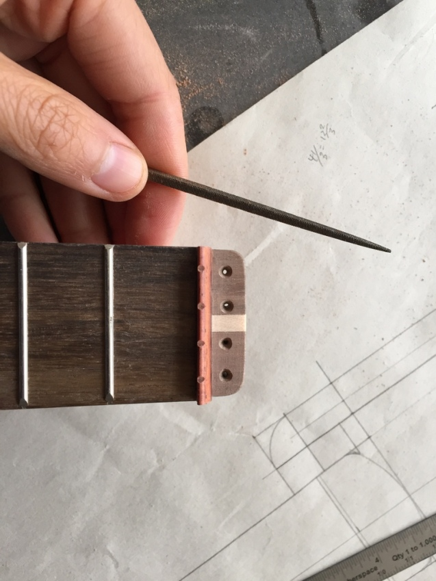 filing notches in the nut for the strings